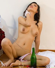 Glamorous Asian bride drinking champagne naked on the floor